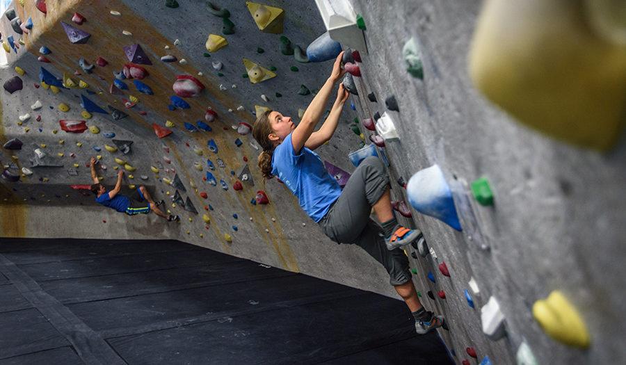 female student climbing rock wall