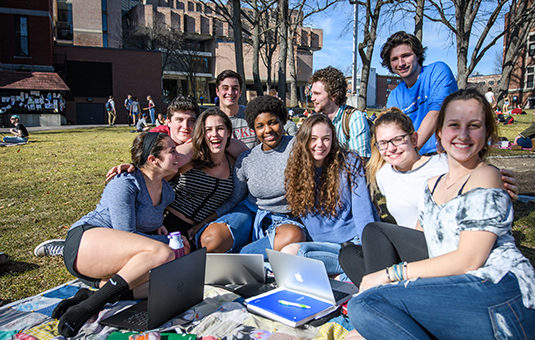students sitting on the green campus grounds on a blanket