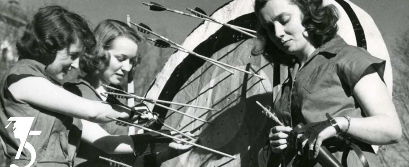 Grey and white photo of girls practicing target practice with arrows