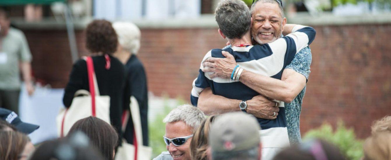 male alumni member giving hug to female alumni member
