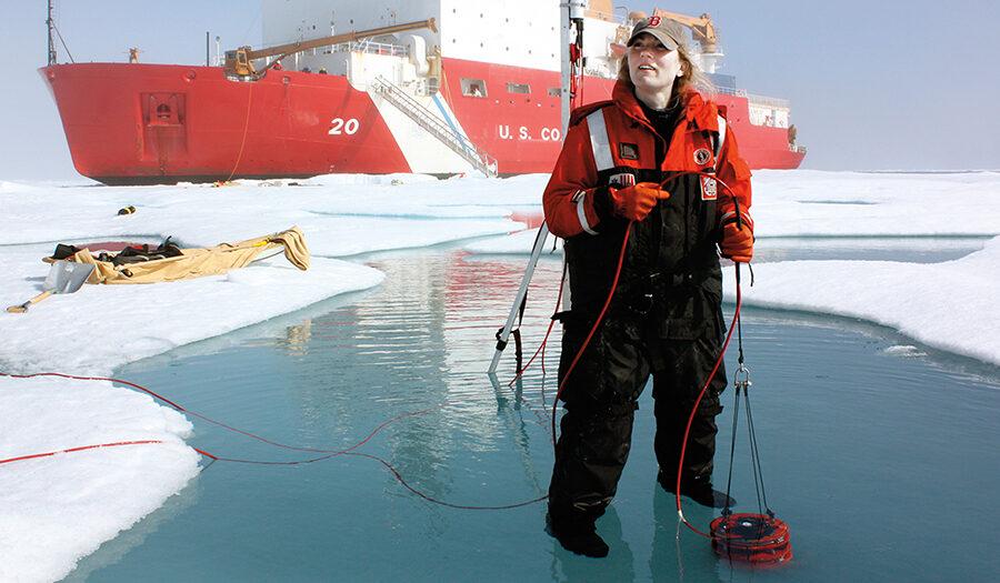 Professor Karen Frey standing on ice with Coast Guard ship behind he