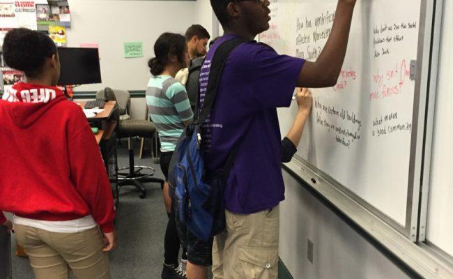 Student writing on chalk board