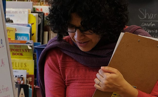 teacher picking out books in classroom