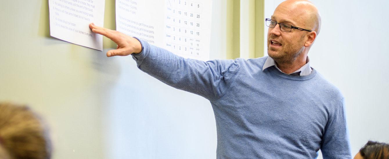 Professor pointing to chaulk boar