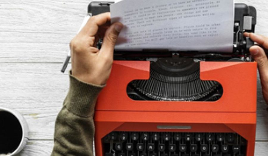 Hands removing paper from typewriter