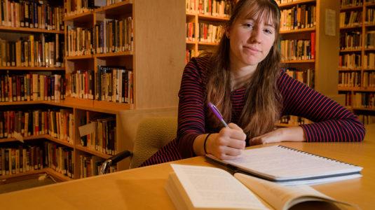 Casey Bush in front of bookshelves