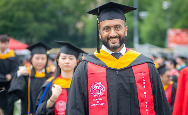 Graduate student smiling with cap and gown