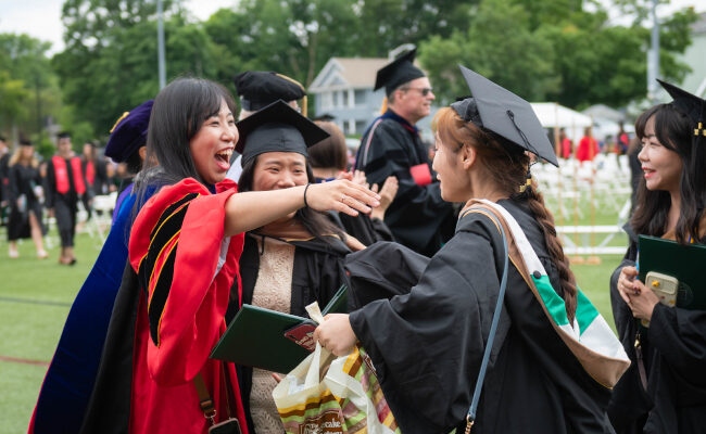 Group of recent graduates hugging each other