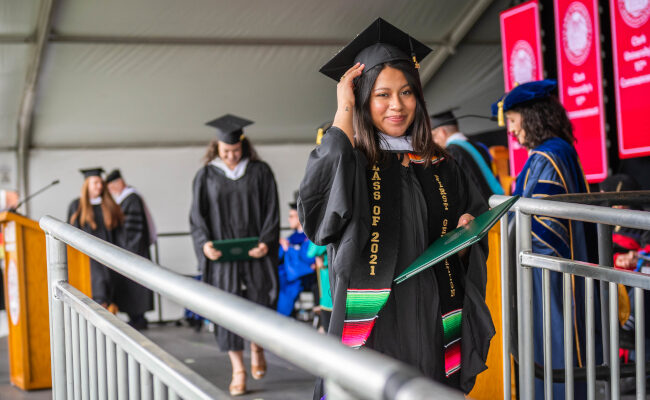 Grad student walking with diploma in hand