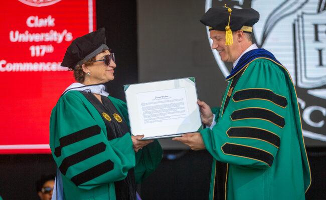 Clark university staff holding diploma up
