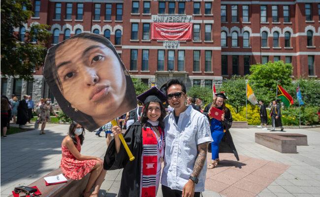 Clark graduate posing with large face cutout