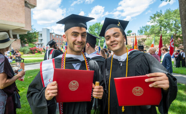 Two students side by side with diploma
