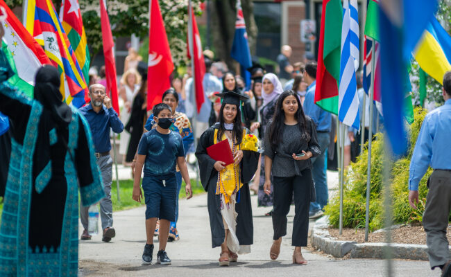 Family walking down walkway with several international flags