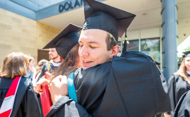 Student with cap and gown hugging friend