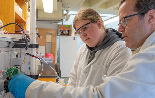 Ph.D. student working with younger student in lab