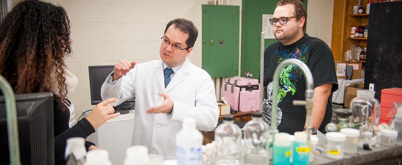 Professor Luis Smith speaks to two students in a chemistry lab