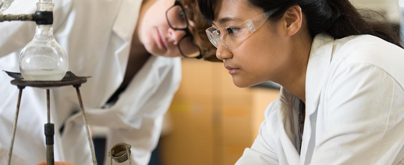 Two female studentslooking at beaker
