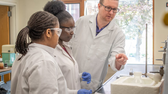Professor Don Spratt coaches Worcester high school students in his lab
