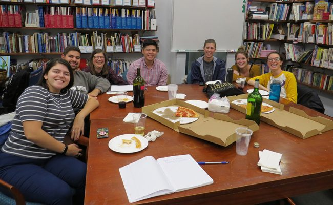 Educators sitting around table with pizza boxes