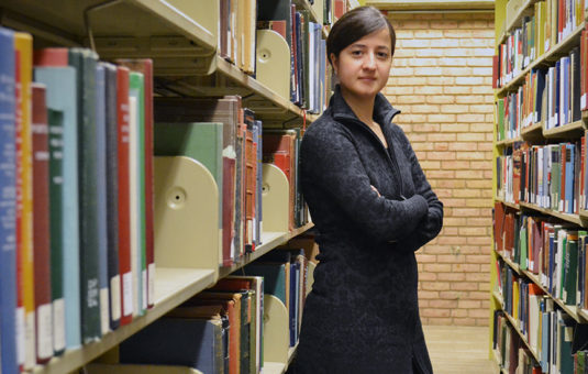 Student standing in book stacks in library