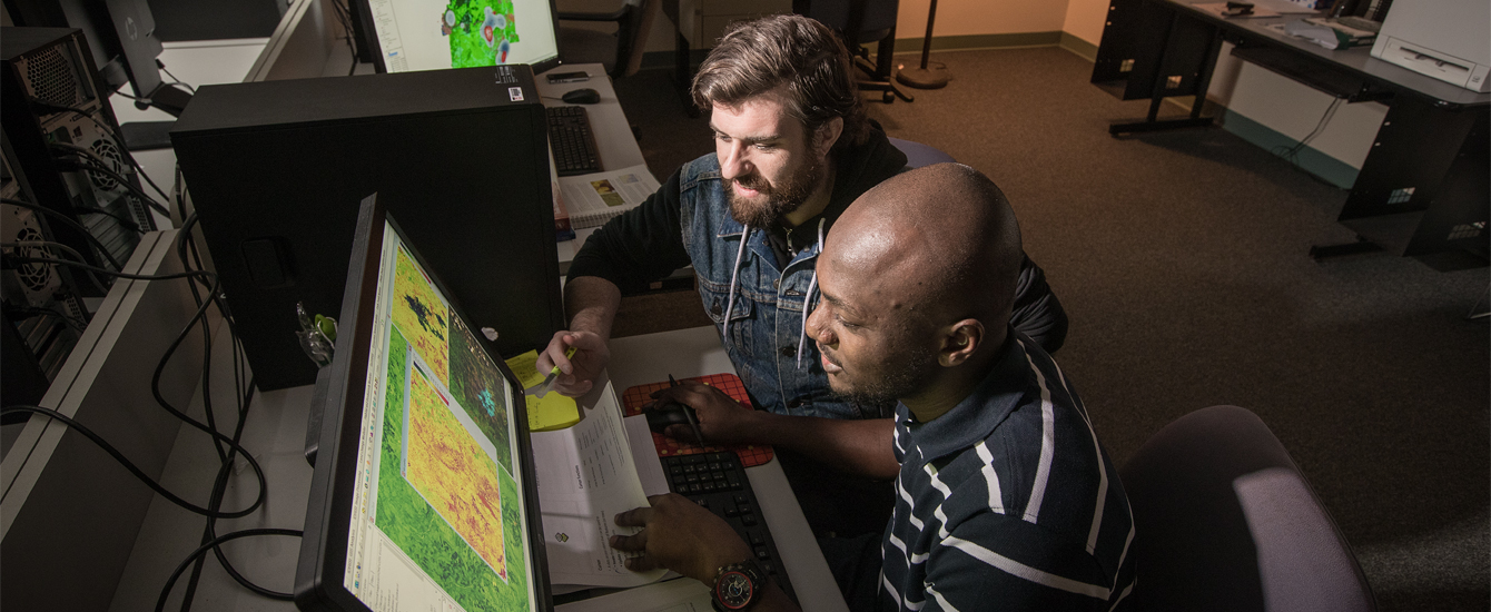 Two students examining map on a computer monitor