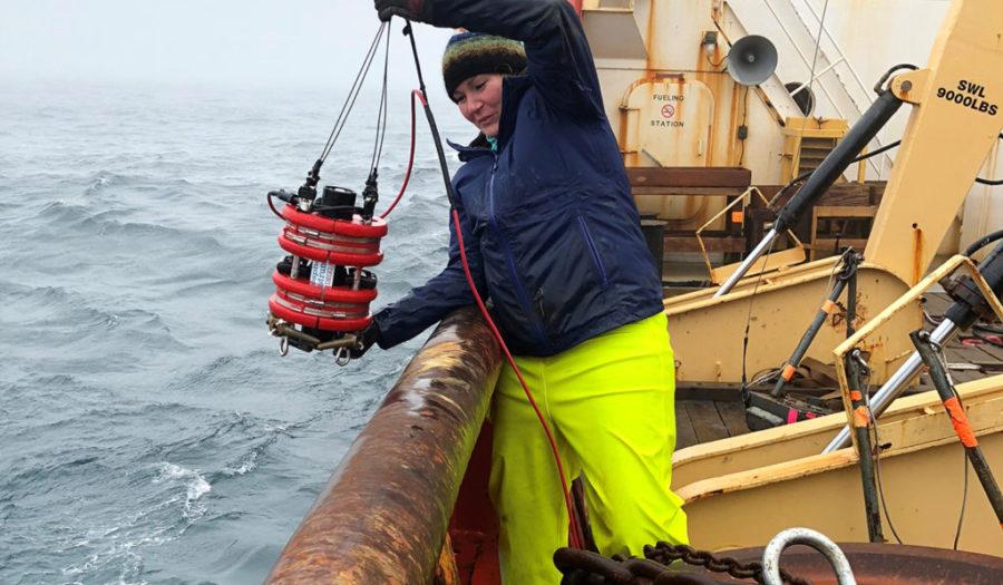 Karen Frey pulling up water sample from ocean