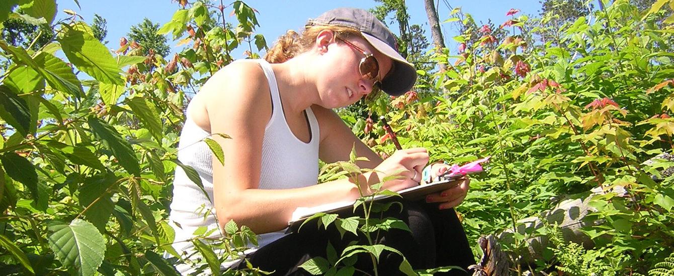 girl sitting in field writing in notebook