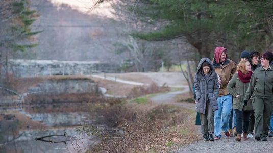 students walking down path near mill
