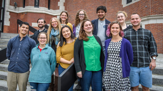 Students in GIS class stand outside on steps