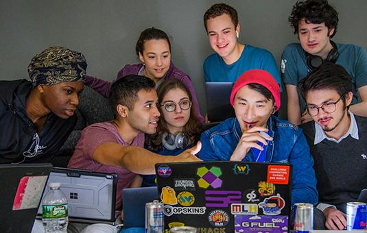 Hackathon students looking at a computer