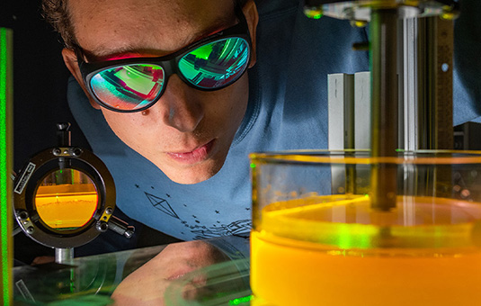 Student with goggles looking at liquid