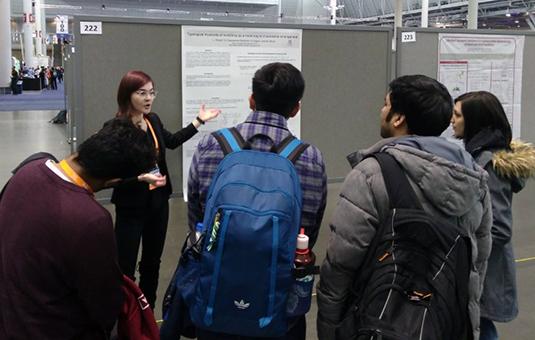 Students gathered around poster presentation
