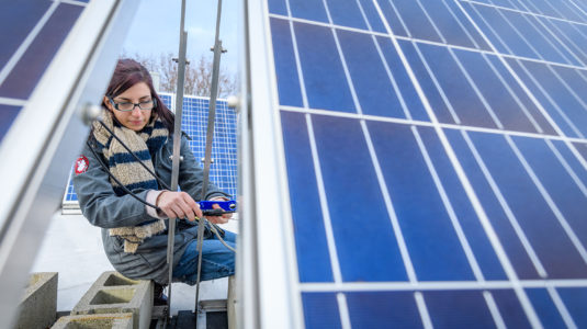 Megan McIntyre works on a solar pane