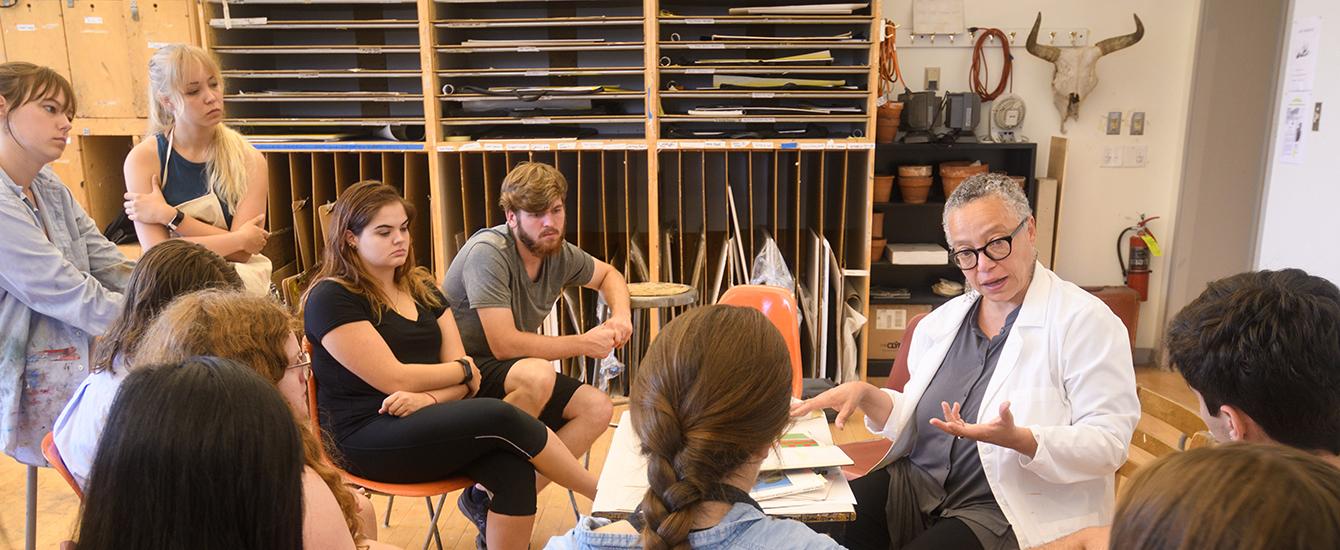 Professor talks to students in studio art class