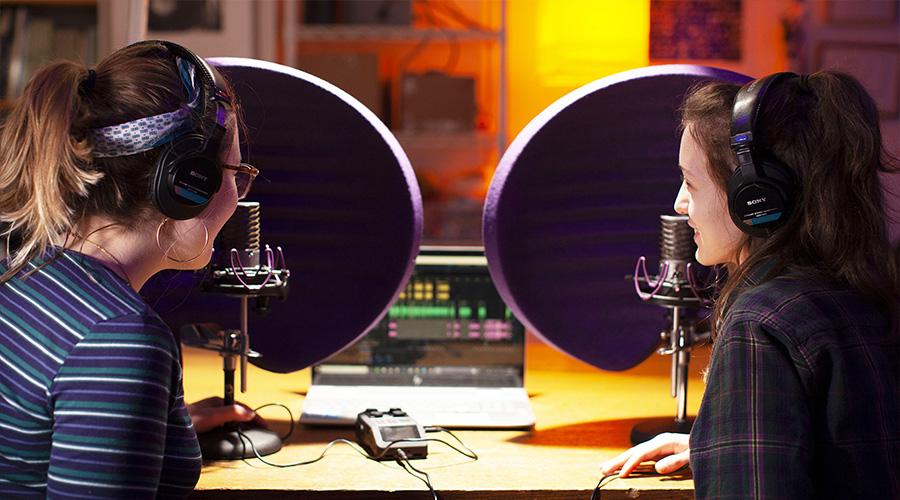 two girls talking to mics in media studio