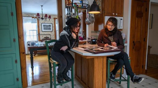 student sitting in kitchen with artist reviewing art