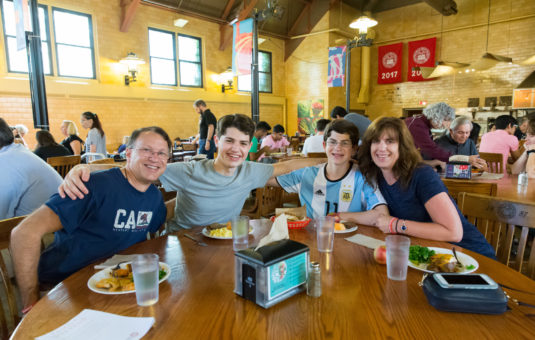 family sitting around dining table in campus center