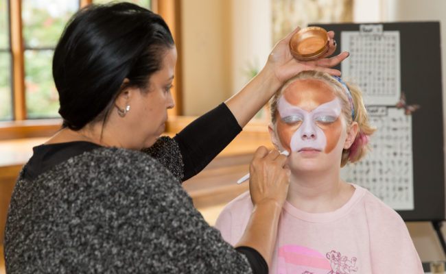 woman painting faces on little girl