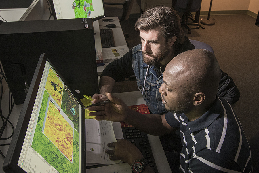 professor and graduate student looking over maps on pc