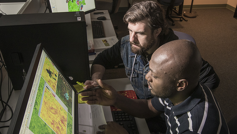 professor with graduate student looking at maps online