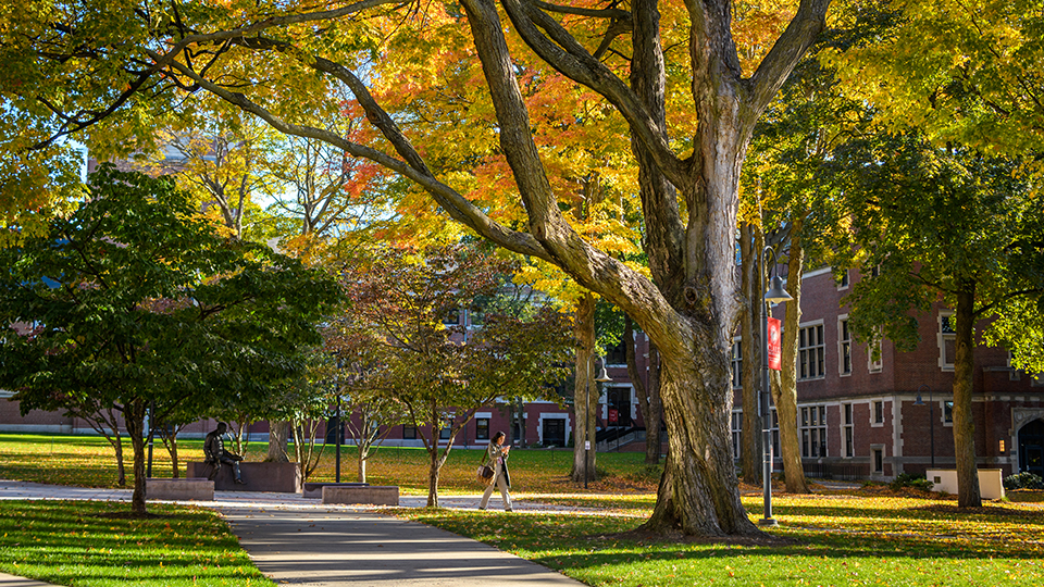 female student walking across campus with fall leaves