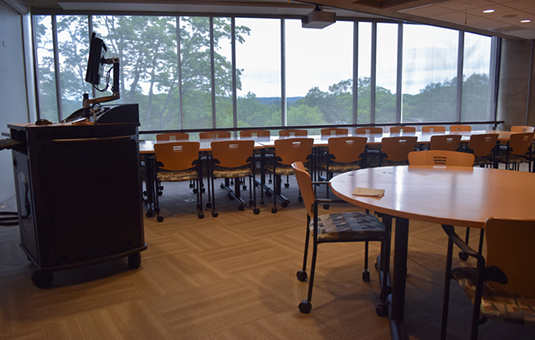 fuller music room with chairs and tables and a podium