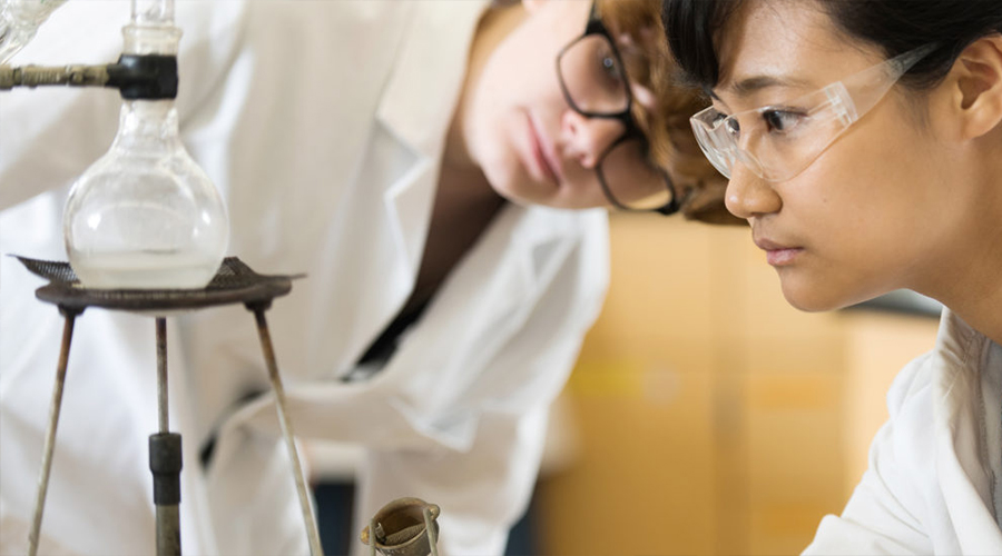female students looking at chemistry lab