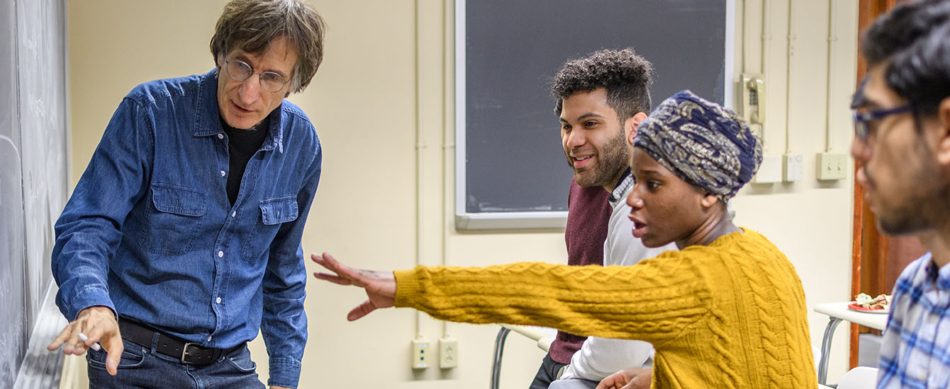 students in class pointing to chaulk board with professor