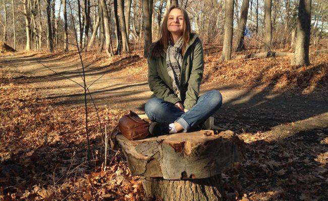 girl sitting on stump