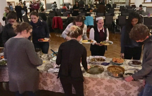 buffet table with people picking food