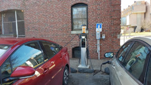 two electric cars plugged into charging station
