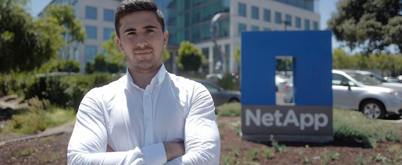 Student standing in front of NetApp sign