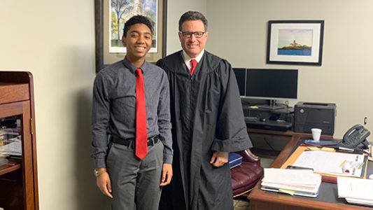 student with judge smiling at camera for job shadowing