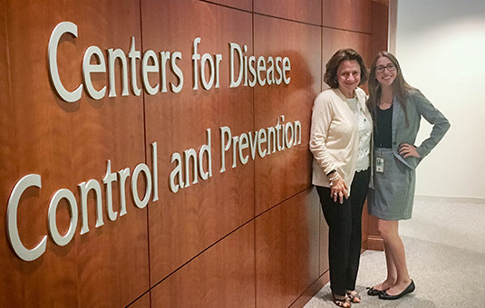 student with director standing in front of sign for centers for disease control office